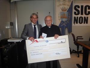 Il presidente Ancit Luigi Pessina consegna l'assegno a don Ettore Rovatti